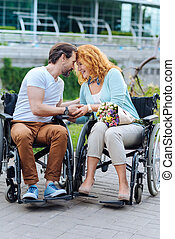Senior loving couple sitting in the wheelchairs outdoors