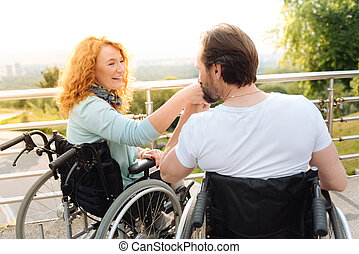Senior loving disabled man kissing a hand of his wife