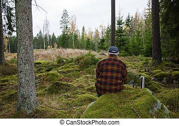 Senior lumberjack sitting in a forest