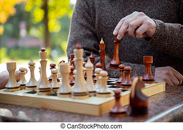 Senior male arm moving statuette on chessboard