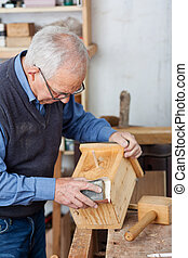Senior male carpenter using sandpaper for polishing birdhouse at worktable in workshop