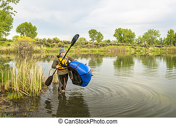 senior male carrying a packraft