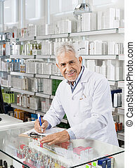 Senior Male Chemist Writing On Clipboard In Pharmacy