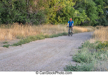 senior male cyclist is riding a touring bike on a gravel trail along the Poudre River in Fort Collins, Colorado, late summer scenery