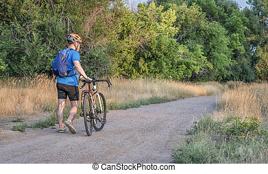 senior male cyclist is riding a touring bike on a gravel trail at Colorado foothills, late summer scenery