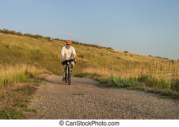 senior male cyclist is riding a touring bike on a gravel trail at Colorado foothills, summer scenery
