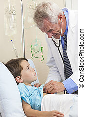 Senior Male Doctor Examining Young Boy Child Patient