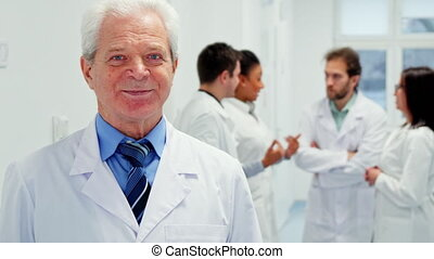 Close up of senior male doctor posing at the hospital. Gray caucasian man in white coat standing against background of multiracial medical team discussing some issues. Aged medical specialist smiling for the camera