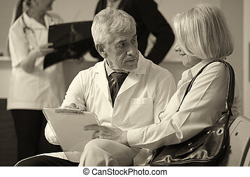 Senior male doctor showing medical results to his female woman p