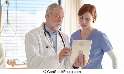 Senior male doctor with tablet standing in hospital room, talking to nurse.