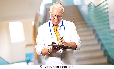 Senior Male Doctor Writing On Clipboard