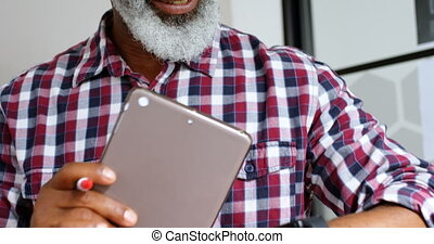 Senior male executive using smartwatch while working on digital tablet 4k