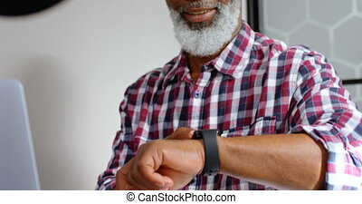 Senior male executive using smartwatch while working on laptop 4k