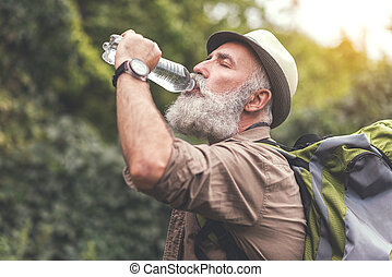 Senior male hiker is very thirsty