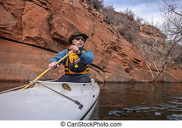 senior male is paddling expedition canoe