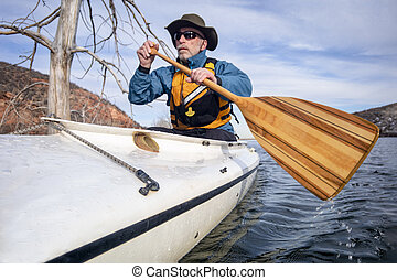 senior male is paddling expedition canoe, focus on a wooden ...