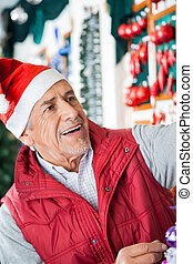 Senior Male Owner Working At Christmas Store