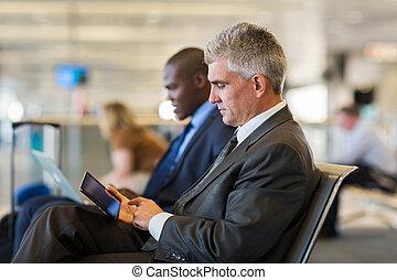 senior male passenger at airport using tablet computer