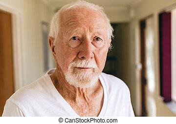 Senior male patient standing in corridor