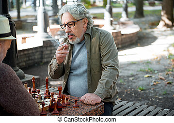 Senior male pensioner thinking of next move in chess game -...