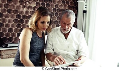 Senior male physiotherapist and young woman with tablet...