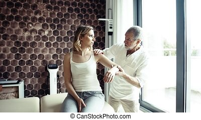 Senior male physiotherapist applying tape on a female...