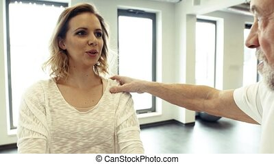 Senior male physiotherapist working with a female patient. -...