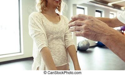 Senior male physiotherapist working with a female patient.