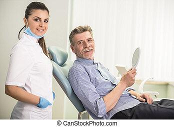 Senior male - Female dentist with his senior client in...
