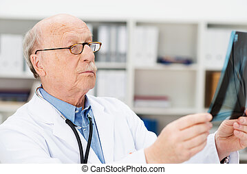 Senior male radiologist checking an x-ray