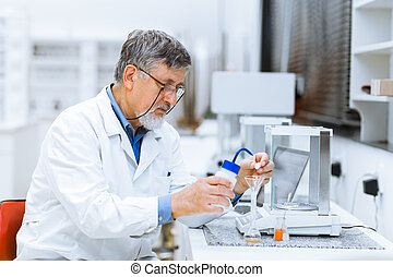 Senior male researcher carrying out scientific research in a...
