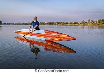 senior male stand up paddler enjoying sunrise