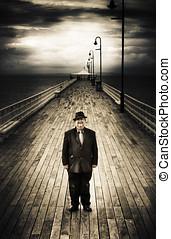 Senior Male Standing On A Pier Promenade