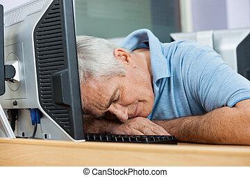 Senior Male Student Sleeping At Computer Desk