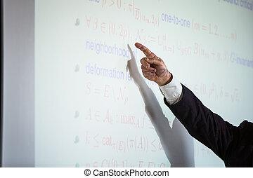 Senior male teacher teaching mathematics, writing on the blackboard