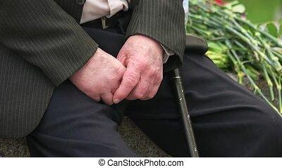 Senior male veteran with cane stick. Close up. Black pants...