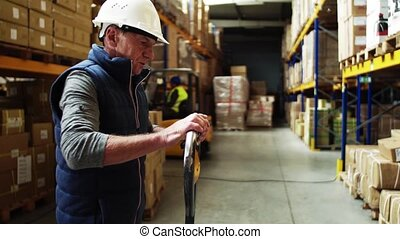Senior male warehouse worker pulling a pallet truck. A...