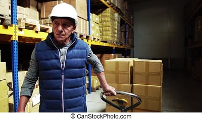 Senior male warehouse worker pulling a pallet truck. -...