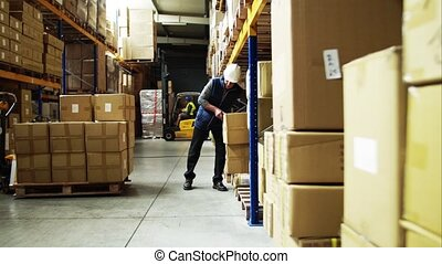 Senior male warehouse worker unloading boxes from a pallet...