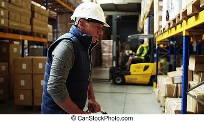 Senior male warehouse worker with a pallet truck, working.