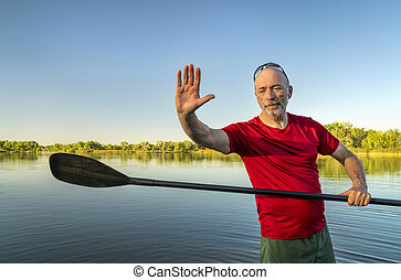 senior male with a stand up paddle