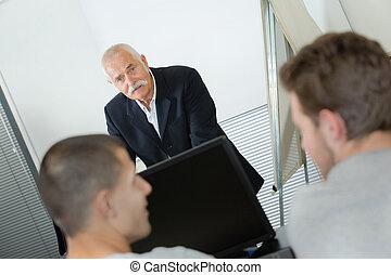 Senior man addressing students