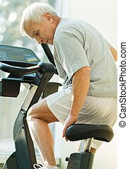 Senior man adjusting seat on a bike machine in a fitness club