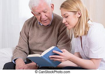 Senior man and caregiver reading interesting book
