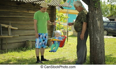 Senior man and father rolls the beautiful baby on a swing. Grandfather with his grandson in the garden of his home