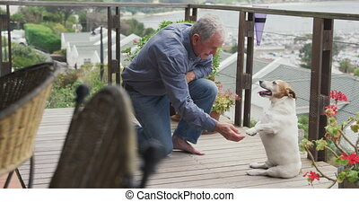 Senior man and his dog on terrace at home