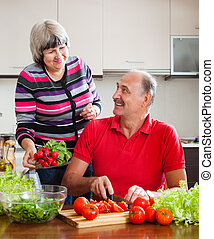 Senior man and mature woman  cooking vegetables