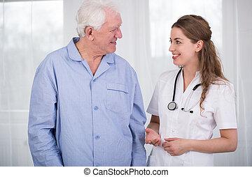 Senior man and pretty nurse