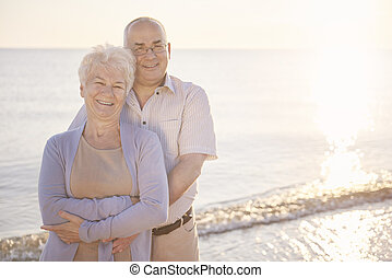 Senior man and woman embracing on the beach