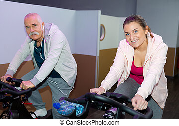senior man and woman exercising at the fitness club